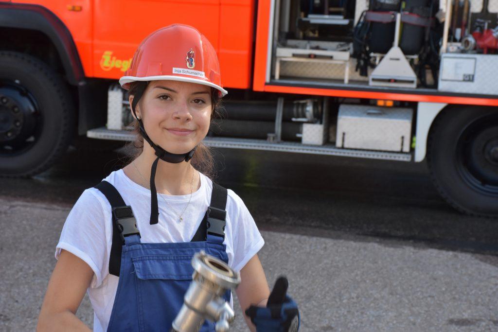 Jugendfeuerwehr-Mitglied vor Löschgruppenfahrzeug